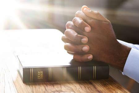 Sonnenlicht fällt auf die Hand des Menschen über das Bibelbuch