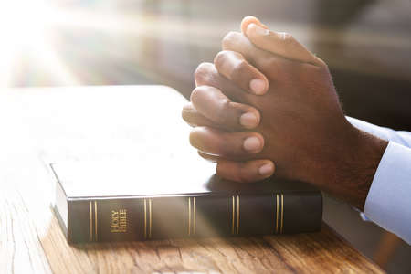 Sunlight Falling On Man's Hand Over Holy Bible Book