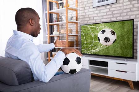 Schockierter Afrikaner, der auf einem Sofa sitzt und ein Fußballspiel im Fernsehen ansieht Standard-Bild