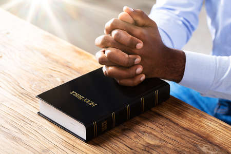 Close-up Of A Man's Praying Hands On Bible Book Over Wooden Desk