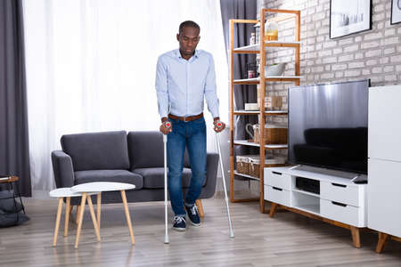 Disabled Man Using Crutches For Walking On Floor