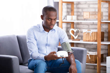 Young Man Sitting On Sofa Checking His Blood Pressure At Home