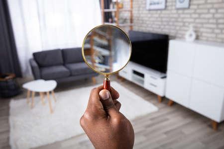 Mann sucht im Haus mit Lupe Standard-Bild