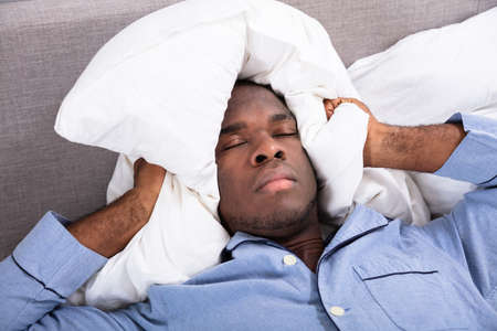 Man Covering His Ears With Pillow While Lying On Bed