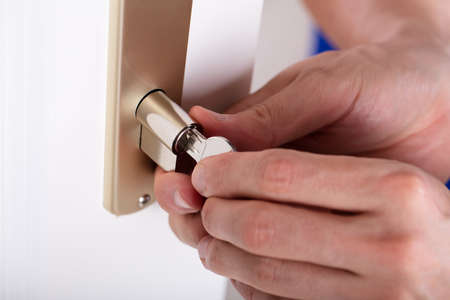 Close-up Of A Carpenter's Hand Inserting Key In Keyhole