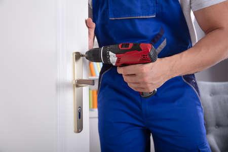 Vista de la sección media de la mano de un hombre que instala la perilla de la puerta con un destornillador inalámbrico Foto de archivo