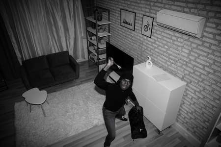 Elevated View Of A Thief In Hooded Sweatshirt Holding Bag And Crowbar In House 免版税图像