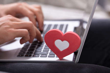Person's Hand Typing On Laptop Keypad With Red Heart