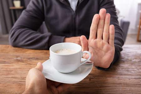 Close-up de la mano de un hombre rechazando una taza de café ofrecida por una persona sobre un mostrador de madera