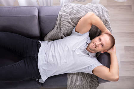 High Angle View Of A Smiling Young Man Resting On Sofa