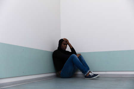 Depressed African Man Sitting Alone On Floor Stockfoto