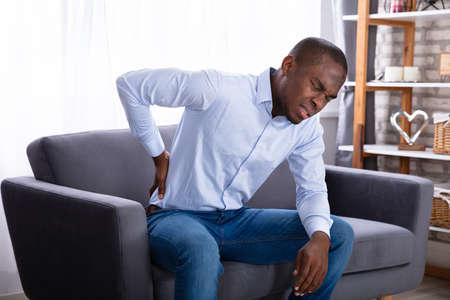Junger afrikanischer Mann sitzt auf dem Sofa und hat Rückenschmerzen