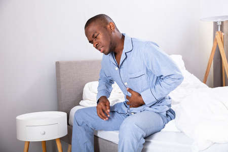 African Man Sitting On Bed Suffering From Stomach Pain