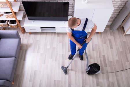 High Angle View Of A Male Janitor Cleaning Floor With Vacuum Cleaner