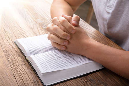 Sunlight Falling On Hand Over Bible While Praying Standard-Bild
