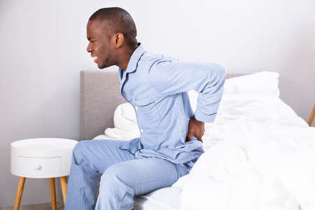 Young Man Sitting On Bed Suffering From Back Pain