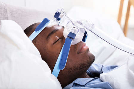 High Angle View Of A Young African Man Wearing CPAP Mask Sleeping On Bed