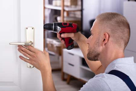 Male Carpenter Installing Door Lock With Wireless Screwdriver