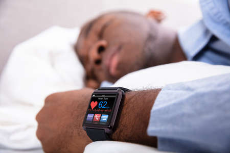 Close-up Of A Man Sleeping With Smart Watch In His Hand Showing Heartbeat Rate