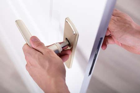 Close-up de la manija de la puerta de fijación de la mano de un carpintero