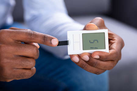Close-up Of A Mans Hand Checking Blood Sugar Level With Glucometer
