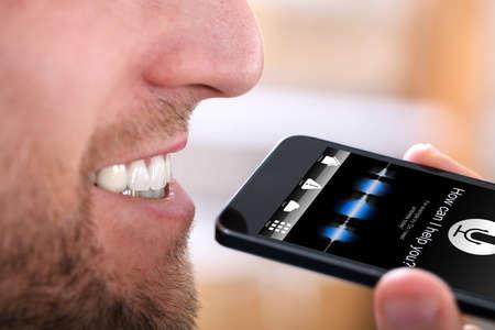 Close-up d'un homme heureux à l'aide de la fonction de reconnaissance vocale sur téléphone mobile