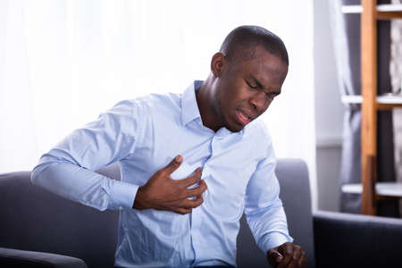 Portrait Of A Young African Man Suffering From Chest Pain Foto de archivo