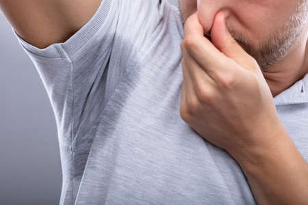Close-up Of A Man With Sweaty Armpit Covering His Nose With Hand Standard-Bild