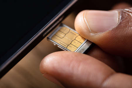 Close-up Of A Person's Hand Inserting Sim Card In Cellphone
