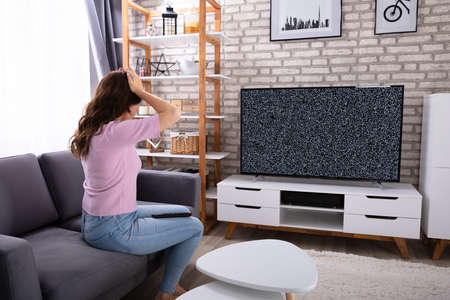 Frustrated Young Woman Sitting On Sofa Looking At Television With No Signal