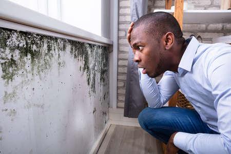 Zijaanzicht van een geschokte jonge Afrikaanse man die naar schimmel op de muur kijkt Stockfoto