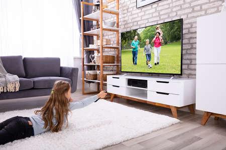Chica acostada sobre una alfombra viendo la televisión en casa Foto de archivo
