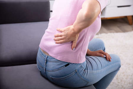 Close-up Of A Woman Sitting On Sofa Having Back Pain Standard-Bild