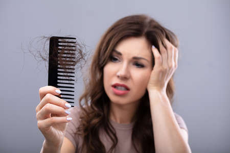 Close-up Of A Worried Woman Holding Comb Suffering From Hairloss Banque d'images - 112391145