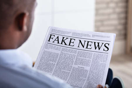 Close-up Of An African Man Reading Fake News On Newspaper