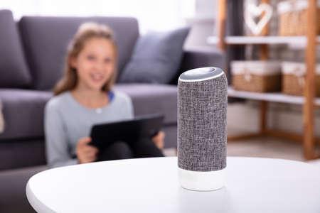 Nahaufnahme eines drahtlosen Lautsprechers auf Möbeln mit Mädchen im Hintergrund Standard-Bild