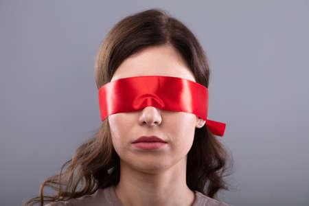Young Woman's Eye recouvert de ruban rouge sur fond gris