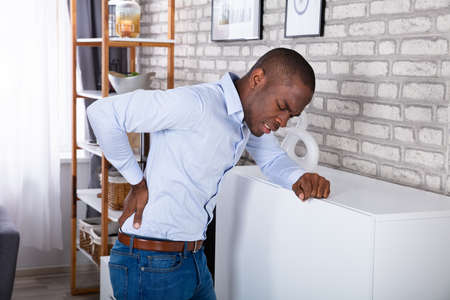 Side View Of A Young Man Leaning On Cabinet Suffering From Back Pain