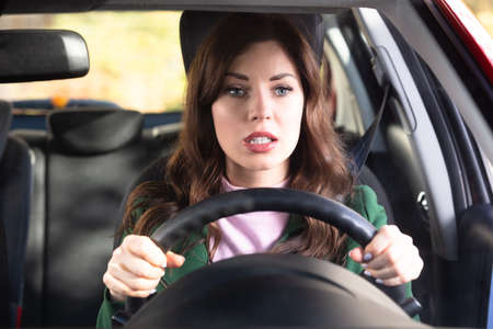 Portrait Of A Shocked Young Woman Driving Car Stock Photo