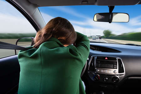 Rear View Of A Young Woman Sleeping While Traveling By Car