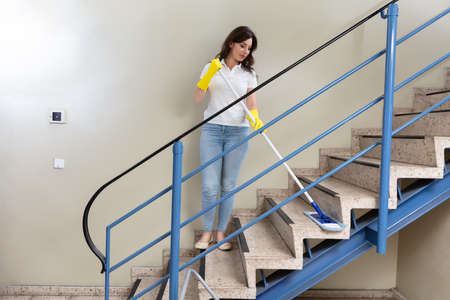 Young Female Janitor Cleaning Staircase With Mop 版權商用圖片