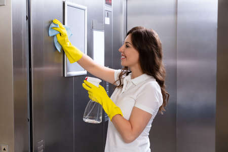 Side View Of A Smiling Young Female Janitor Cleaning Elevator With Duster Standard-Bild - 112391237
