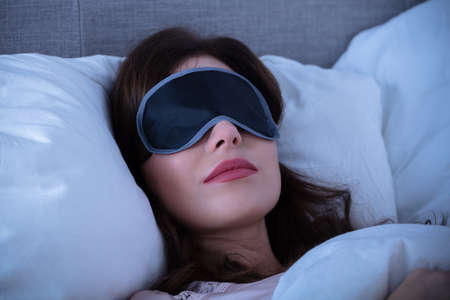 Close-up Of Beautiful Young Woman Sleeping On Bed With Eye Mask