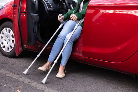 Disabled Woman With Crutches Coming Out Of A Red Car Stockfoto