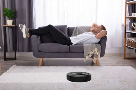 Young Man Lying On Sofa With Robotic Vacuum Cleaner Over Carpet 免版税图像