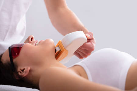 Close-up Of Beautician Hand Giving Laser Depilation Treatment To Young Woman Face Stock Photo