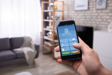Close-up of a Man's Hand à l'aide de l'application Smart Home sur téléphone mobile à la maison