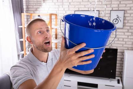 Close-up of a Young Man Holding Bucket tandis que les gouttelettes d'eau fuient du plafond à la maison