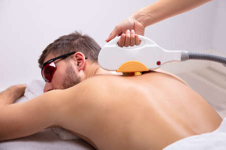 Close-up Of Man Receiving Laser Epilation Treatment By Beautician In Spa