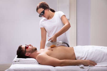 Young Female Beautician Giving Laser Depilation Treatment On Relaxed Mans Chest Stock Photo
